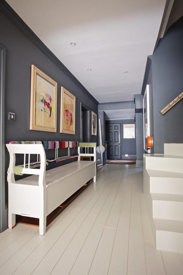 decoration couloir long et étroit aux murs latéraux et au mur du fond peints en gris, en contraste avec le blanc du plancher, de l'escalier et du banc d'entrée
