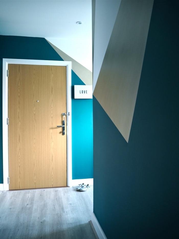 des motifs graphiques réalisés avec de la peinture bleu canard et beige pour un couloir moderne plein de dynamisme