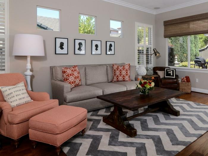 fauteuil avec tabouret couleur saumon, tapis chevrons, sofa gris, table de salon en bois, peinture murale grise, coussins déco