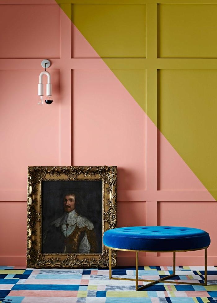 mur en couleur saumon et moutarde, joli motif graphique, tabouret bleu, portrait, tapis patchwork