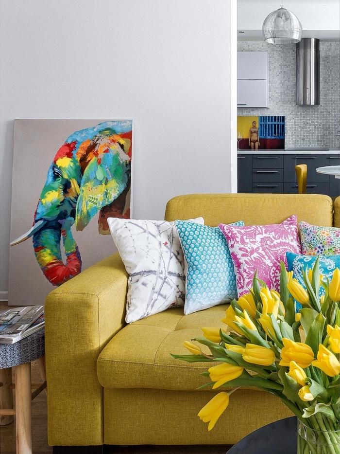 accents flashy dans un salon gris clair, modèle de canapé jaune moutarde couvert de coussins en couleurs aux motifs ethniques