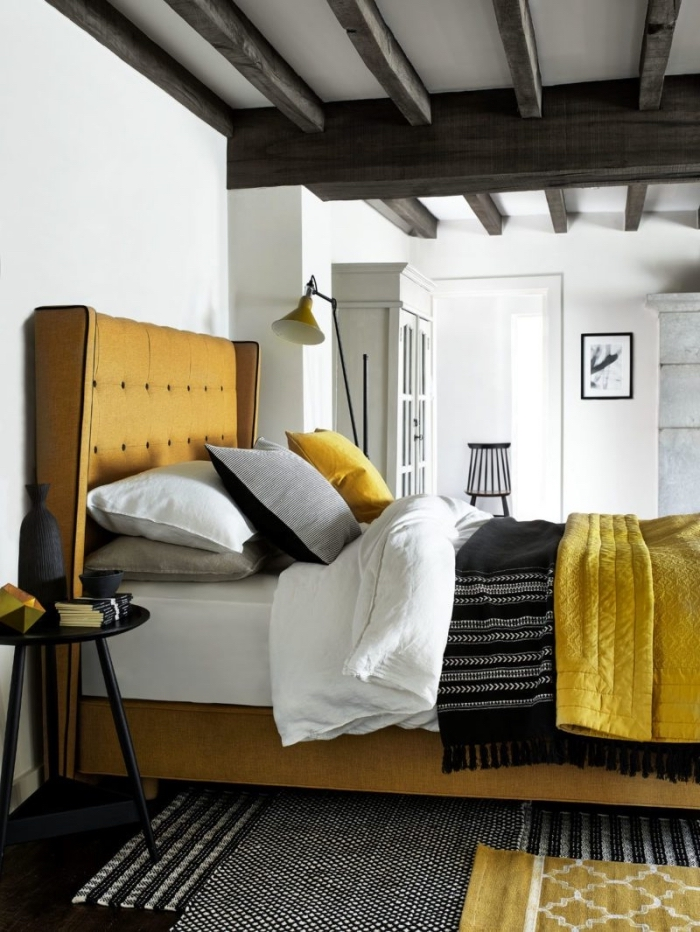 déco de chambre cozy aux murs blancs et plancher noir avec grand lit de couleur jaune moutarde, modèle plaid bohème chic noir avec frange
