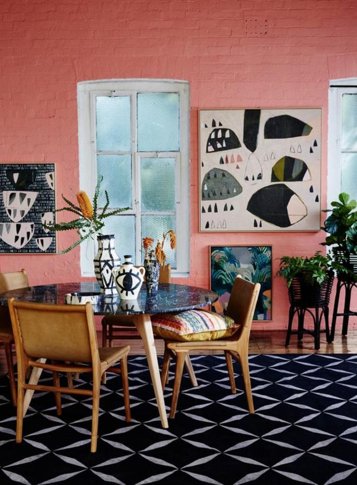 tapis noir motif géométrique, chaises vintage en bois autour d'une table ronde marbrée, plantes vertes, mur en briques peint en couleur saumon