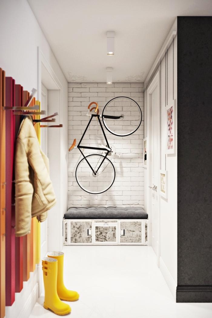 couloir d'entrée de style scandinave avec des touches de couleur sur le porte-manteau mural, peinture blanche mur en briques blanches