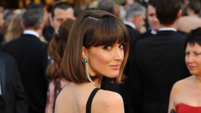 femme avec une coupe carré lisse, frange lisse, longues boucles d'oreilles, robe avec bretelles