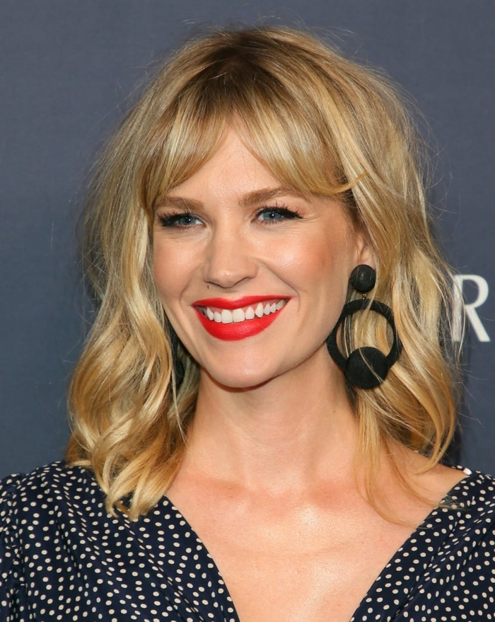 cheveux blonds, carré mi long ondulé, frange des deux côtés, rouge à lèvres couleur vive, chemise pointillée