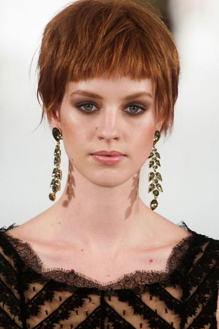 coupe carré plongeant court, boucles d'oreilles pendantes, cheveux roux, robe noire, décolleté dentelle