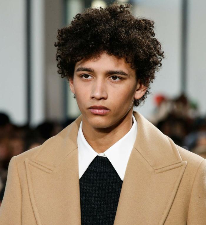 cheveux crépus homme, veste beige, chemise blanche, pull noir, coupe homme mi long