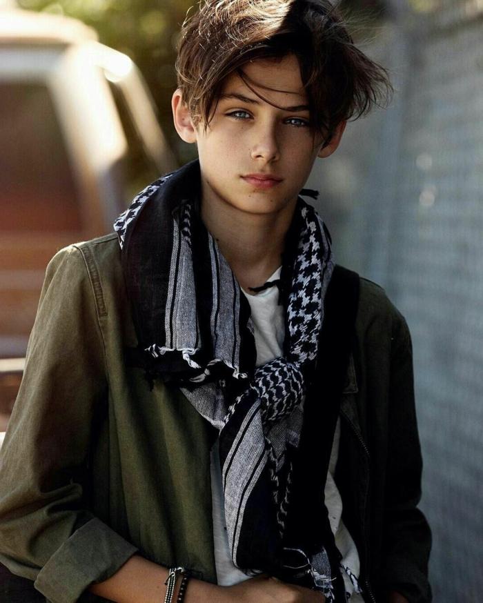 coiffure garcon cheveux mi longs au niveau des oreilles, foulard gris et noir, veste denim vert, t-shirt blanc