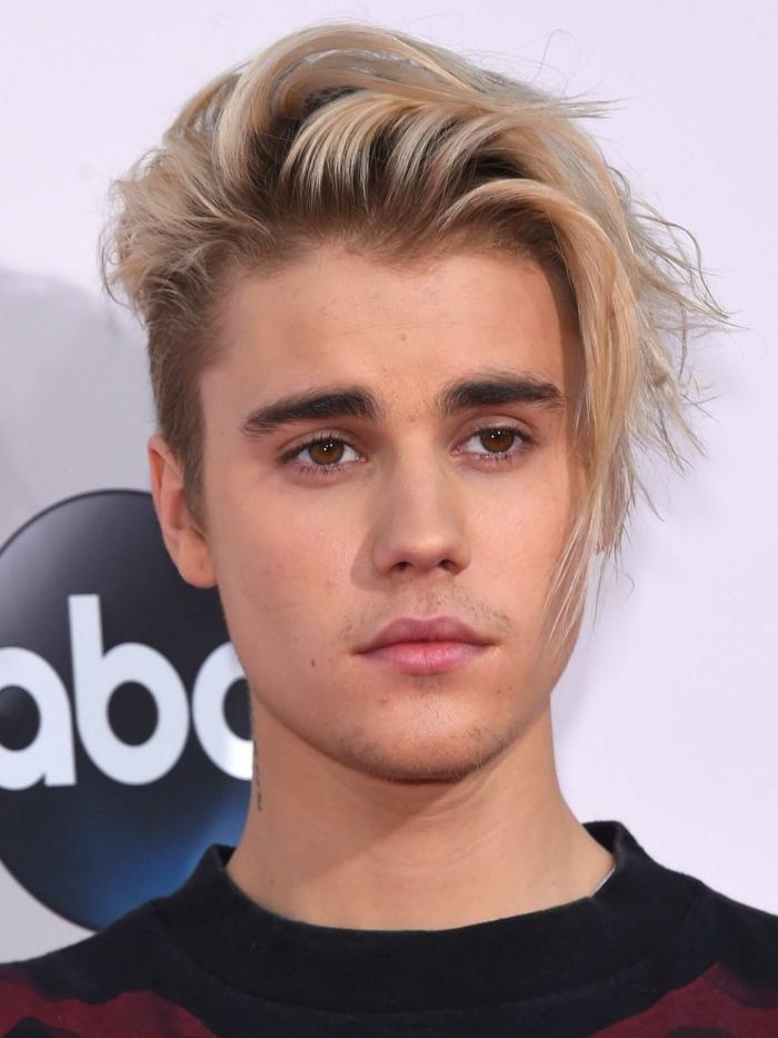 Justin Bieber, cheveux blonds, yeux couleur noisette, frange mise de côté volumineuse