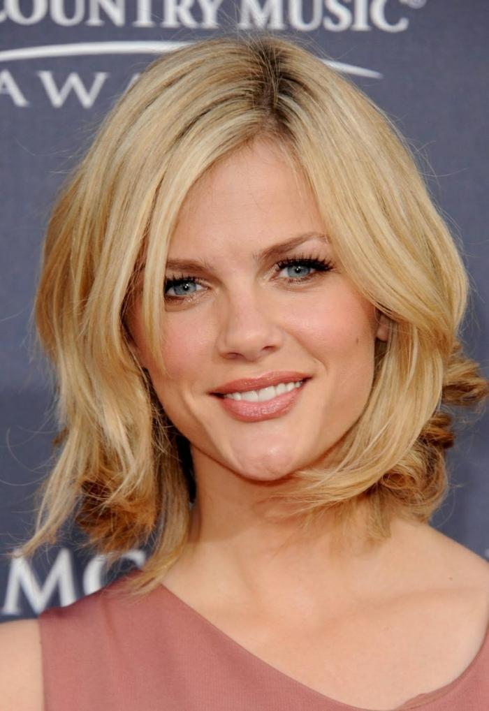 frange asymétrique, coupe de cheveux femme 50 ans, yeux bleus, coloration cheveux blond