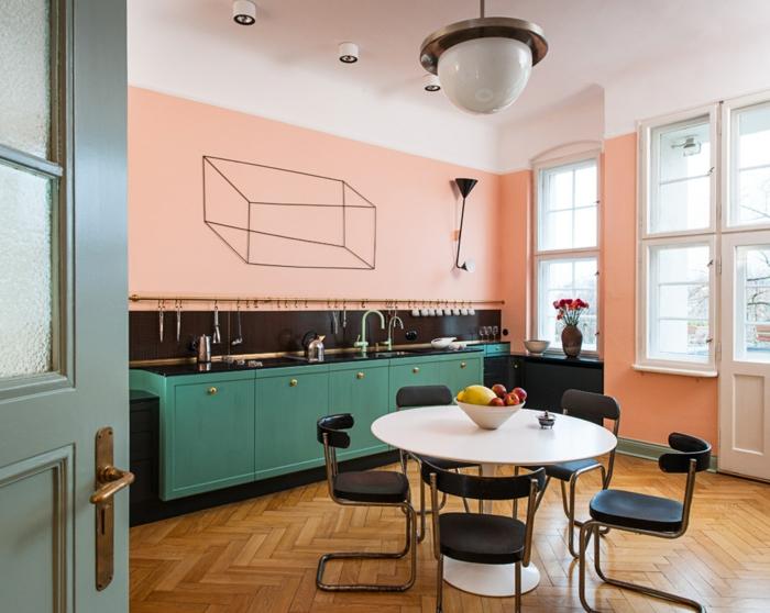 cuisine en bois, vert menthe et corail, plafonnier blanc, table ronde blanche, chaises noires, armoires de cuisine vertes