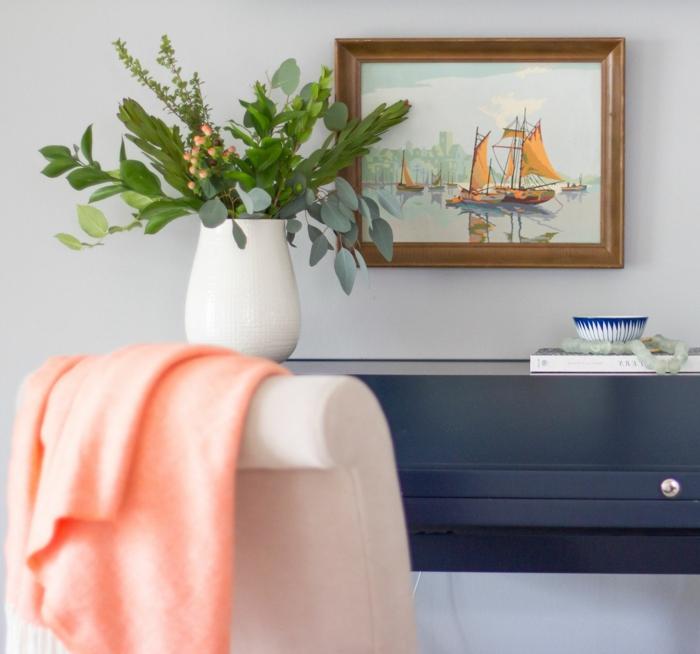 plaid rose, fauteuil blanc, vase blanc, plantes vertes, tableau peinture encadré, console gris anthracite