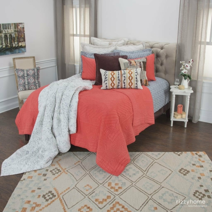 jeté de lit couleur pêche, plusieurs coussins décoratifs, table de chevet, grand plaid gris, murs bleus