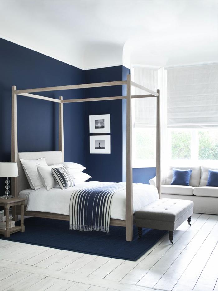 chambre en bleu et blanc, lit baldaquin, tabouret gris, sol en planches de bois, sofa blanc, coussins bleus