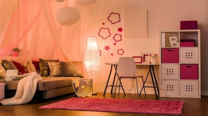 chambre d'enfant couleur pêche, tapis rose, plafonniers en papier, étagère en blanc et rose, petit bureau, guirlande lumineuse