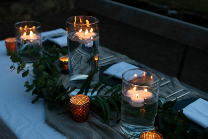 chemin de table jetable en toile de jute, bougeoirs originaux, vases avec bougies flottantes, guirlande de feuilles vertes