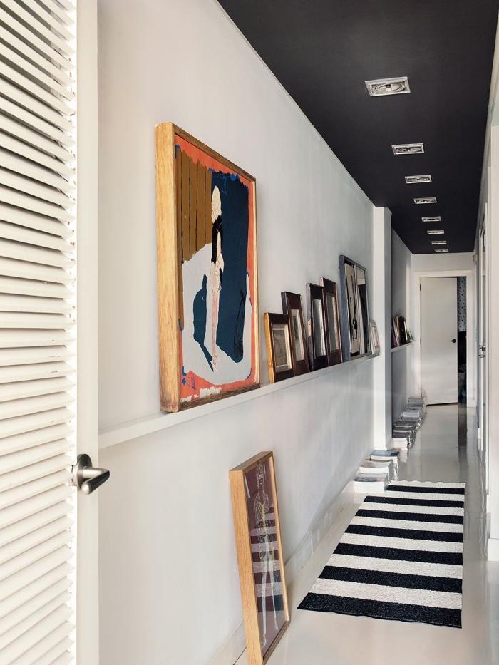 decoration couloir long et étroit en noir et blanc avec une étagère de cadres artistique et un plafond peint noir mat pour un joli effet graphique