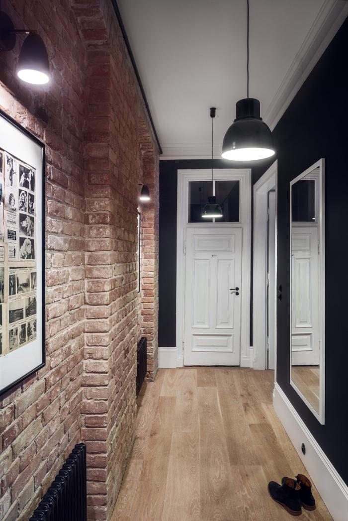 deco couloir de style loft industriel au mur en briques qui s'accorde parfaitement avec le noir du mur opposé et l'éclairage industriel