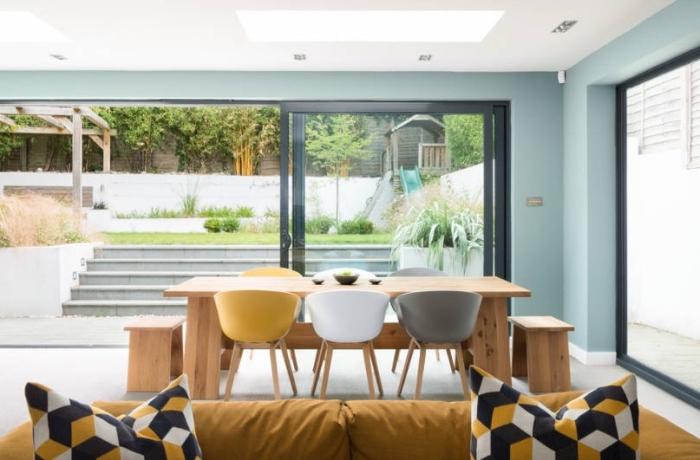 design intérieur salon aux murs pastel avec plafond blanc et fenêtres cadre noir, mobilier salle à manger bois avec objets de couleur moutarde