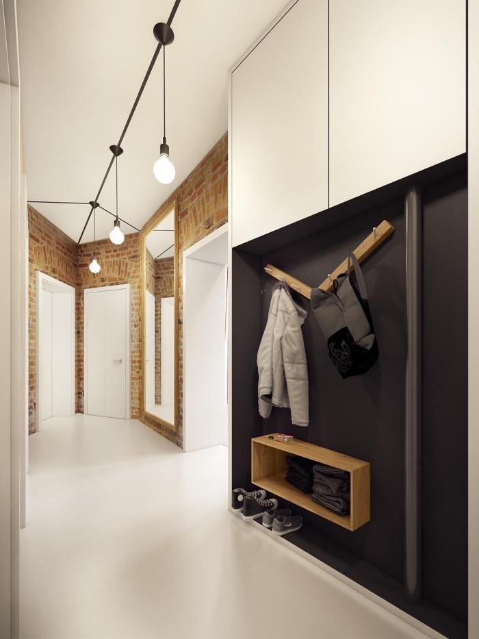 un meuble entrée couloir en noir et blanc mat qui s'inscrit parfaitement dans un couloir de style scandinave aux murs en papier peint imitation briques