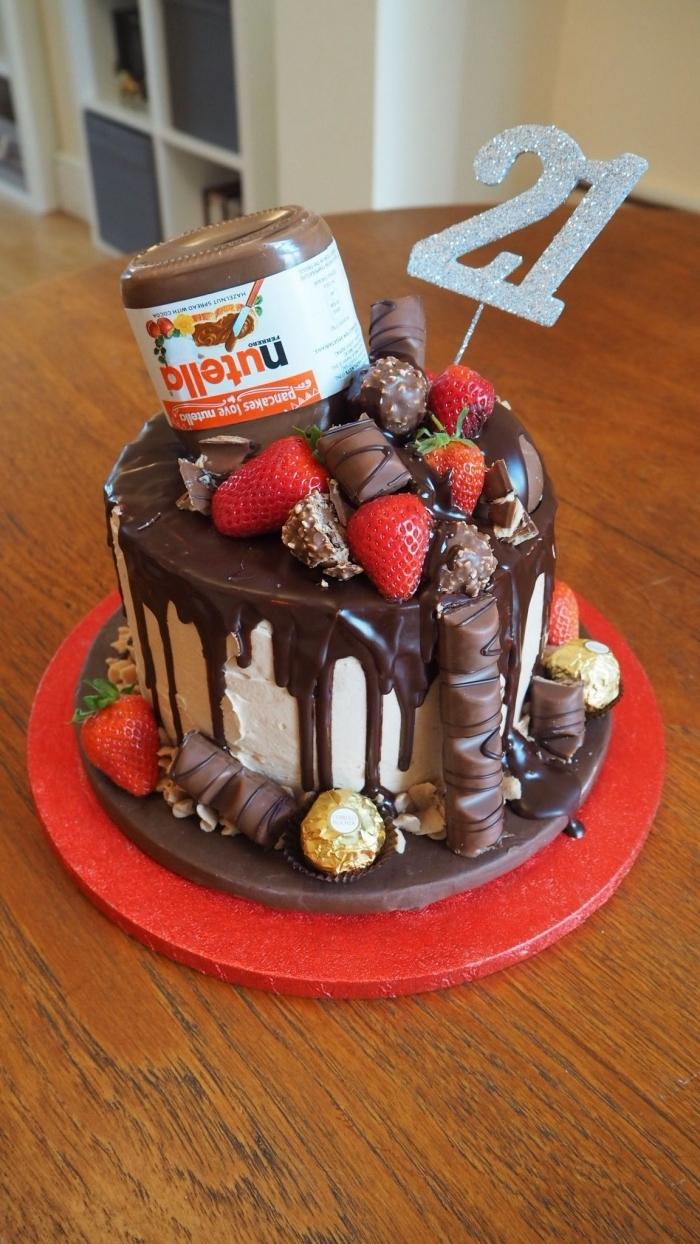 idée de gateau anniversaire original au glaçage coulant de chocolat avec un joli déco de faux pot de nutella, de barres chocolatées et de fraises