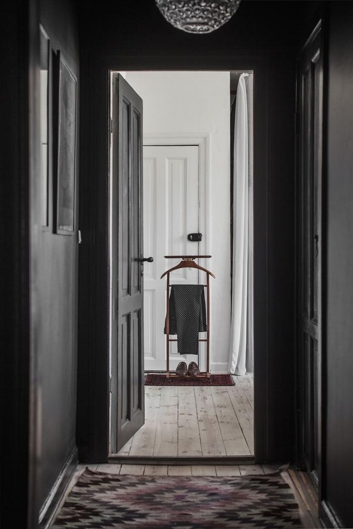 deco couloir sobre de style scandinave avec des murs et des portes peintes dans la même couleur noir mat en contraste avec l'intérieur blanc