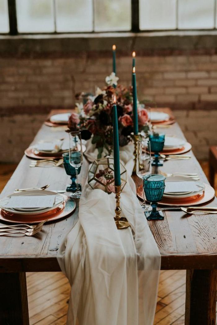 table en bois, assiettes et sous assiettes arrangées, grandes bougies turquoises, ustensiles dorés, verres bleus