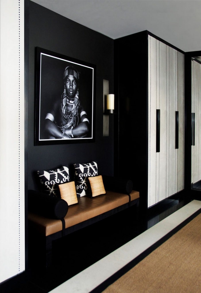 un hall d'entrée noir et blanc aux accents déco ethniques chic avec une belle assise en cuir à côté du placard, decoration couloir d'entrée noir et blanc
