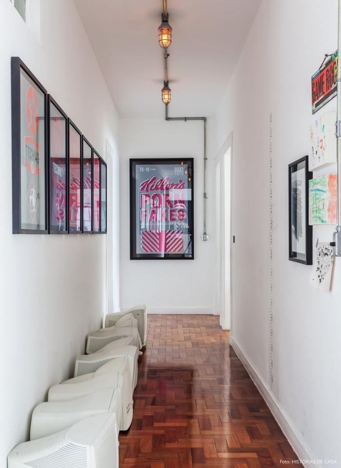 déco couloir étroit aux murs blancs dynamisé par un mur d'affiches encadrées et une lampe murale industrielle