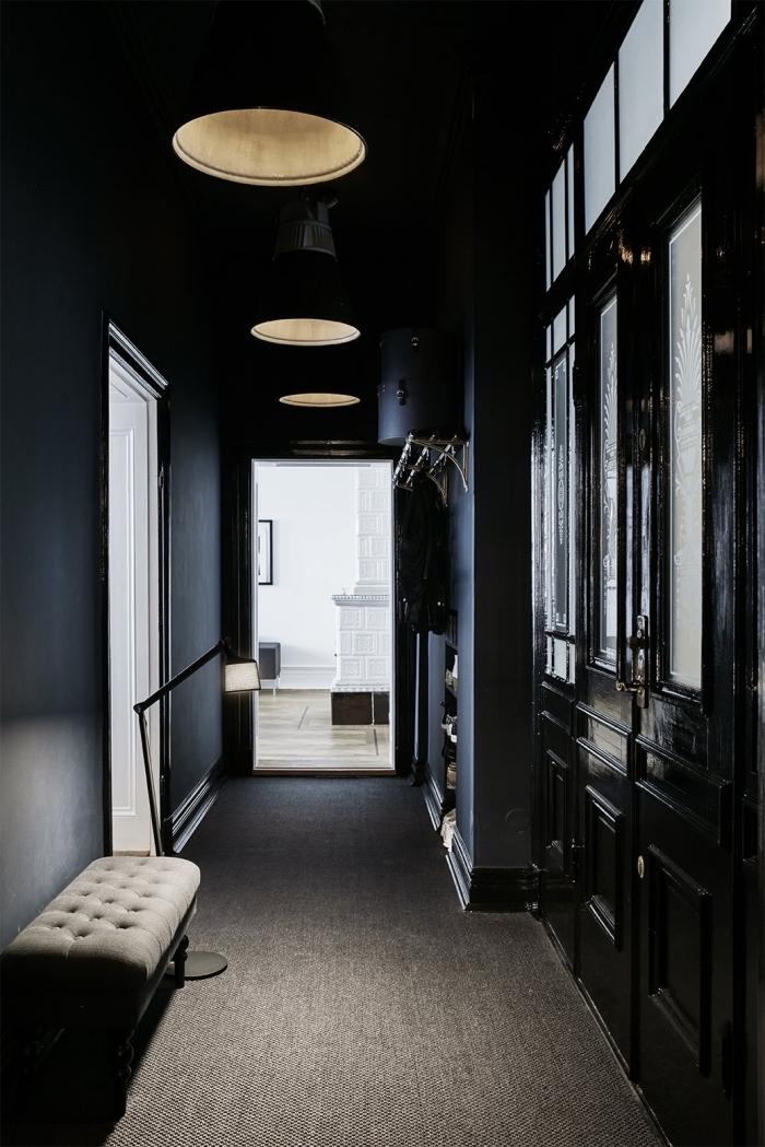 déco couloir étroit de style haussmannien aux murs peint en noir mat qui donne sur un salon blanc