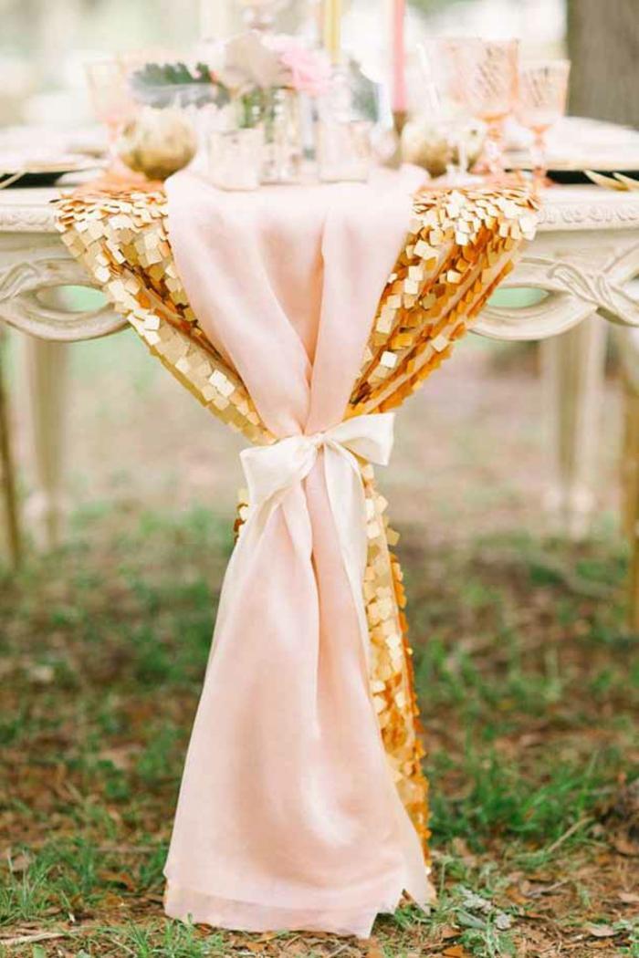 chemin de table en toile rose, décorée de paillettes, table vintage chic, bougies et verres, mariage à l'extérieur