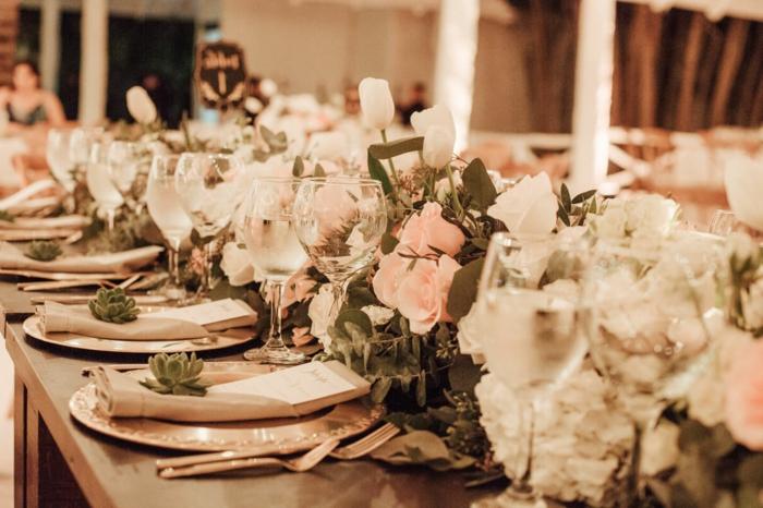 petites succulentes posées sur les assiettes plates, ustensiles cuivrées, chemin de table en roses et fleurs blanches
