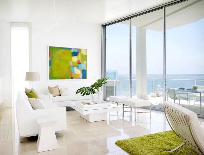 salon blanc avec grandes fenêtres au plafond blanc et plancher de carrelage beige, accents de couleur vert anis