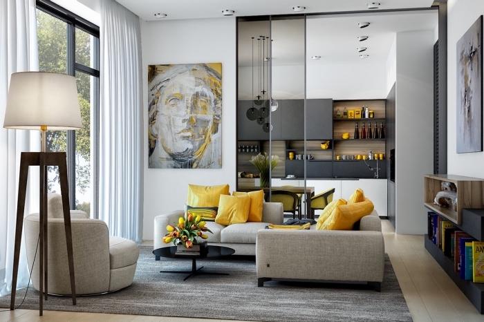 idée déco jaune et gris dans un salon moderne ouverte vers la cuisine, mobilier salon fauteuil et canapés gris clair décoré de coussins jaunes