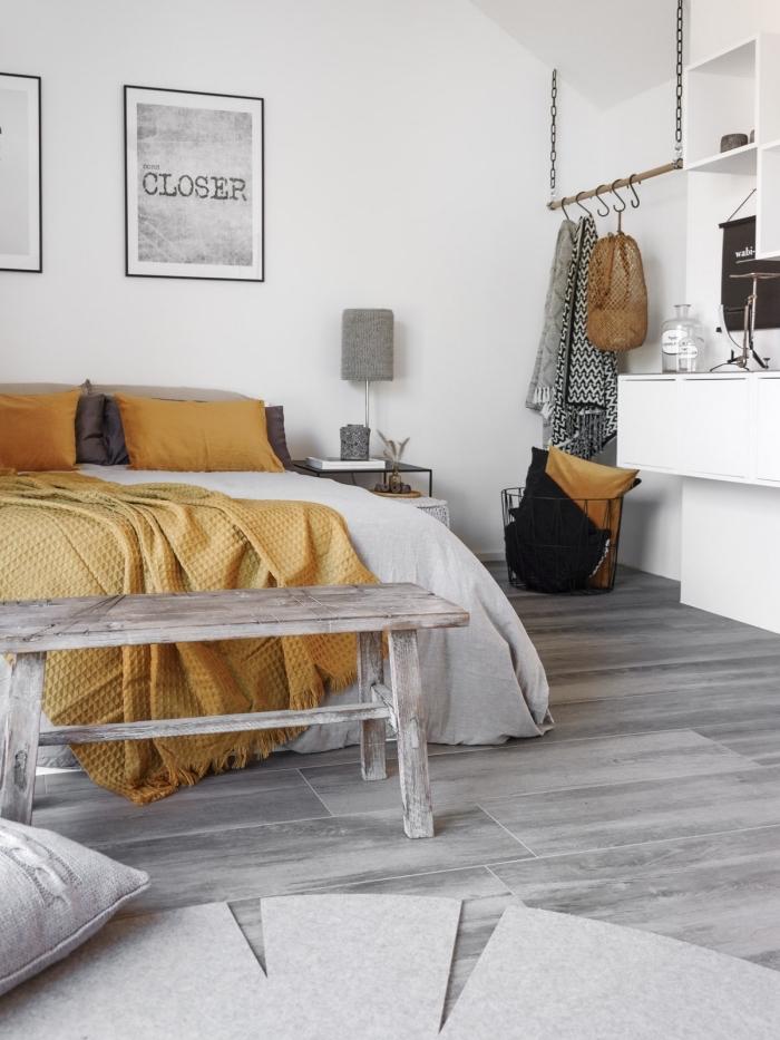 chambre à coucher de style minimaliste aux murs blancs et parquet gris clair, linge de lit et coussins décoratifs de couleur jaune moutarde