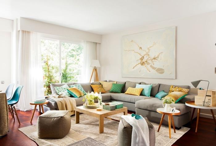 les couleurs qui vont ensemble dans un salon cozy, pièce blanche avec parquet foncé et grand canapé gris clair décoré de coussins en couleurs jaunes et vertes