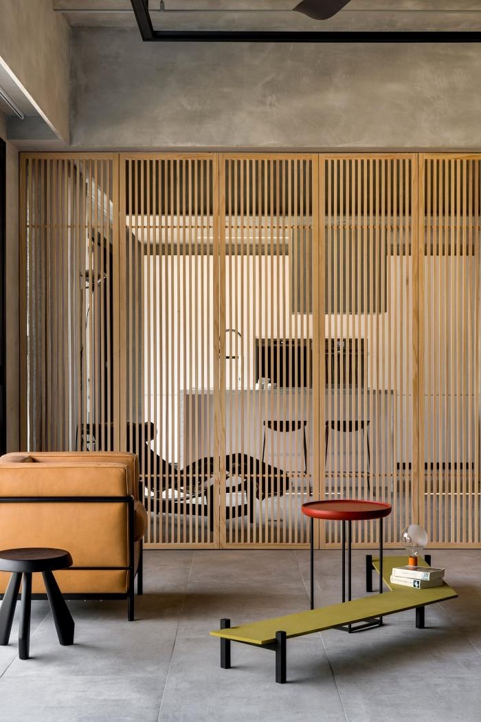 aménagement salon au plafond haut de style industriel avec meubles design, idée comment séparer un appartement loft en zones avec claustra bois