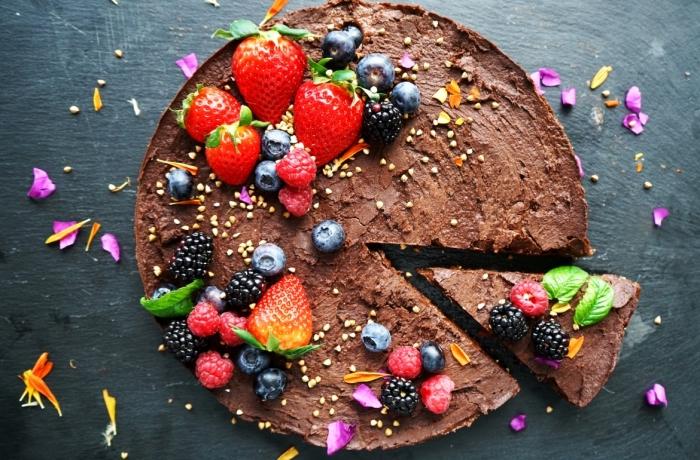 recette vegan de gateau sans farine au glaçage riche de trois chocolats décoré de fruits rouges et de fleurs comestibles