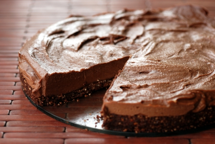 recette vegan de gateau sans farine façon cheesecake avec une base de dattes et de noisettes garni de crème au chocolat vegan