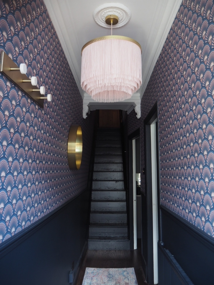 déco couloir étroit élégante et féminine aux murs associant papier peint à motifs stylisés en bleu et violet et peinture noire