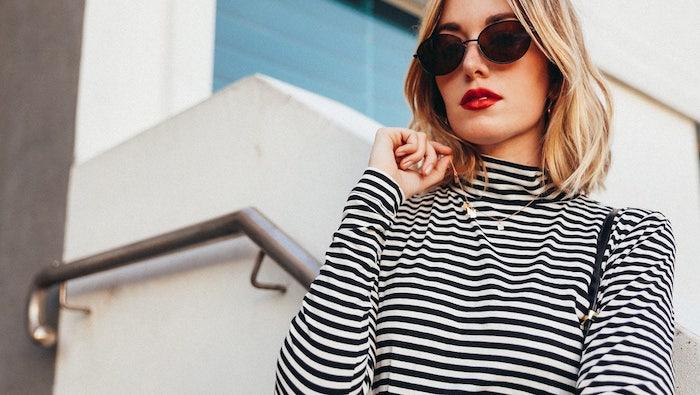 modele de carré plongeant mi long sur cheveux blond façon beach waves, pull femme noir et blanc, lunettes de soleil tendance femme