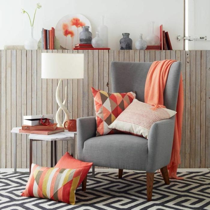 décor avec couleurs douces, couleur saumon et gris pâle, coussins à grands triangles, table blanche, lampe de table blanche, tapis géométrique