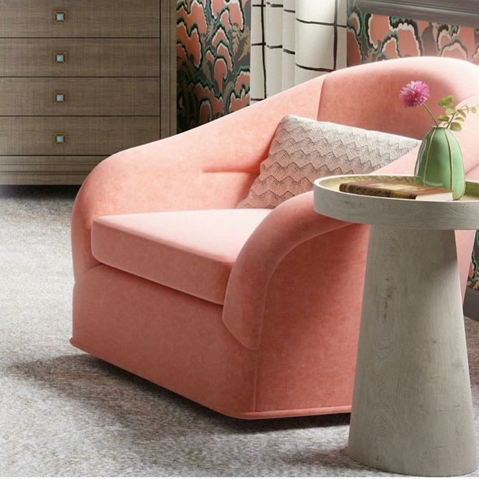 fateuil couleur flamingue, petit vase vert, tapis gris, buffet en bois, table de chevet e gris clair