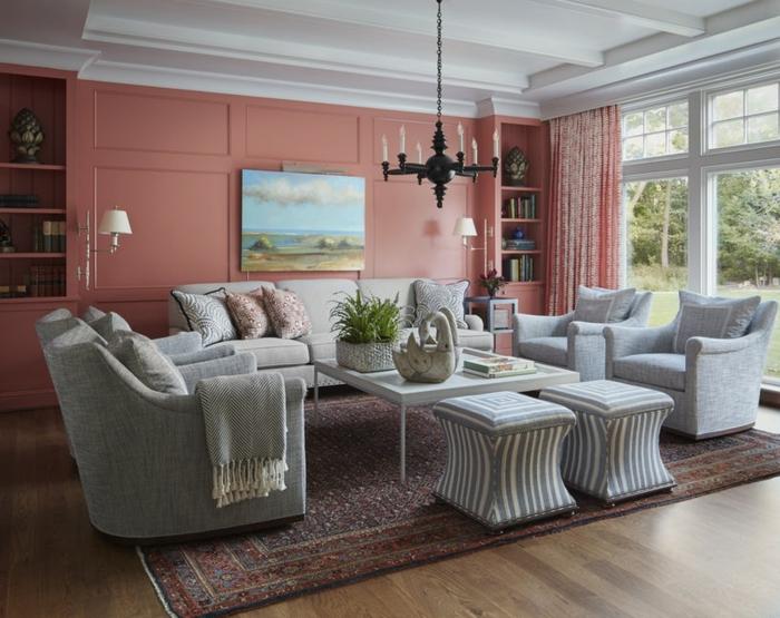 joli salon, fauteuils gris clair, tapis persan, mur peinte en couleur pêche, paysage, chandelier moderne