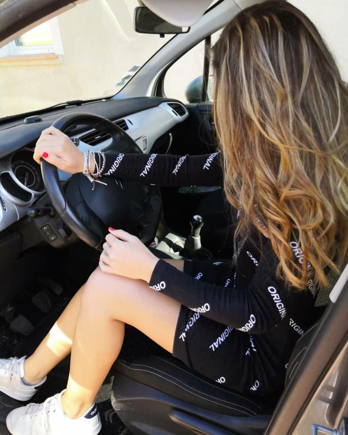 Fille dans sa voiture, tenue avec baskets, comment associer des baskets blanches avec une robe noire courte à manche longue