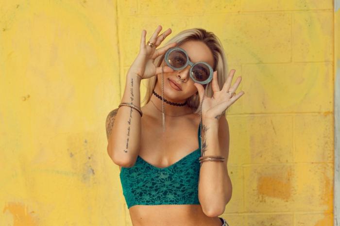 Jaune mur pour fond d'une photo ensoleillée, fille mignonne, lunettes de soleil rondes, accessoires et tatouages, blonde fille