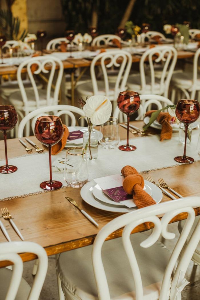 jolie table de mariage, flûtes à champagne, assiettes et sous-assiettes, serviette de table en noeud orange, chaises élégantes blanches