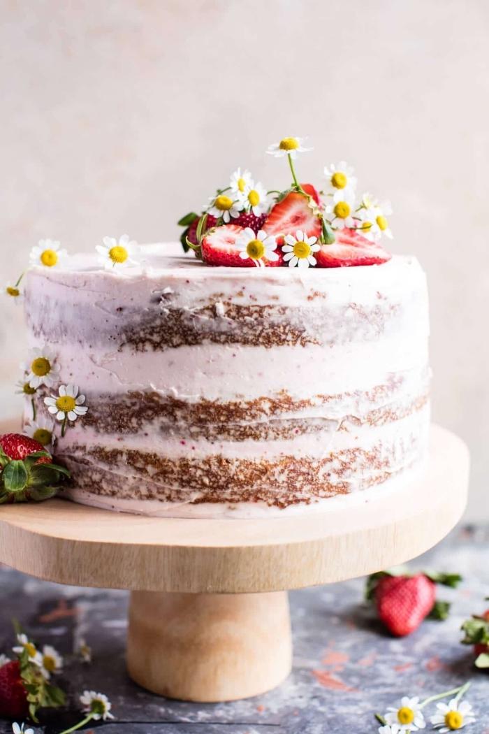 gâteau étagé aux carottes, à la noix de coco au glaçage mascarpone et crème beurre, avec un joli décor naturel de fraises et de camomille