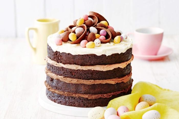 idée de gateau anniversaire adulte composé de quatre génoises au chocolat recouvertes de crème pâtissière au nutella et au chocolat blanc, le tout avec un joli décor d'oeufs au chocolat